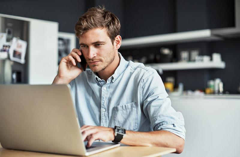 Mann snakker i telefon og ser på laptopskjerm